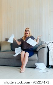 beautiful blond woman with glasses sits on the couch and throws up paper