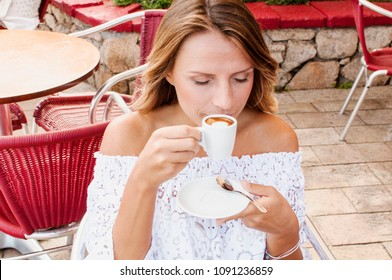 Beautiful blond woman having her morning espresso in summer terrace in Italy