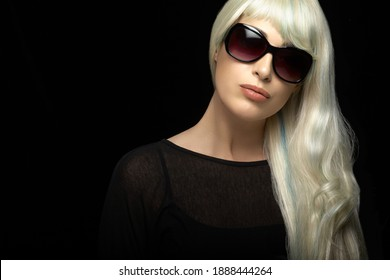 Beautiful blond woman with healthy long silver hair, wearing black sunglasses, looking at camera. Beauty portrait on black background with copy space for text.