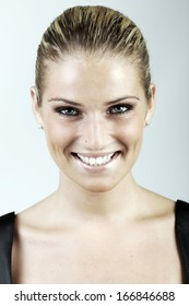 Beautiful blond woman with her hair tied back neatly looking directly at the camera with a beaming friendly smile