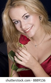 Beautiful blond woman holding red rose and smelling them