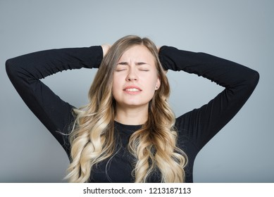 beautiful blond woman in hysterics holding her head in isolation over gray background