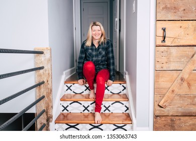 beautiful blond woman laughing sitting in the stair of a modern house