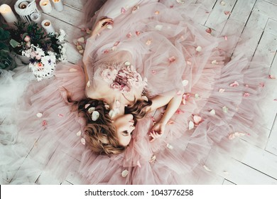 beautiful blond woman lies on a wooden white floor in a beautiful soft pink dress of tulle in flowers, strewn with rose petals