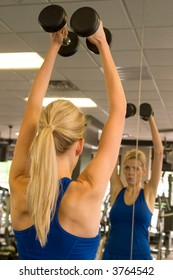 Beautiful blond woman lifting weights while looking at image in mirror in a fitness center. Image in mirror is out of focus.