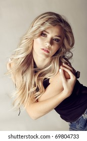 beautiful blond woman with long curly hair looking seriously at the camera, holding herself by the shoulders