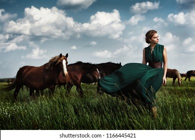 beautiful blond woman in a long green dress stands in a field among the herd of brown horse stallions. beautiful artistic emotional photo, wind develops her dress, cloudy sky