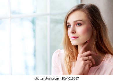 beautiful blond woman with long hair resting at home by the window