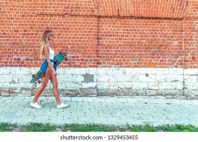 Beautiful blond woman with long hair walks brick wall, summer in city. White bodysuit with jeans, longboard board. Free space for text. Concept girl hipster goes event weekend walk to meeting.