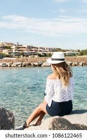 Beautiful blond woman looking on the sea, back view