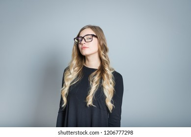 beautiful blond woman looks arrogant, isolated over gray background