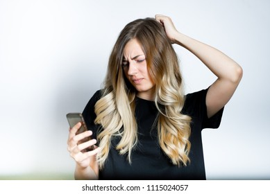 beautiful blond woman looks at the phone confusedly, isolated studio photo on the background