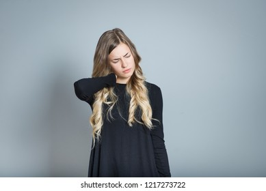 beautiful blond woman with neck pain, isolated over black background