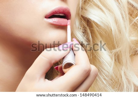 beautiful blond woman paints lips with lipstick