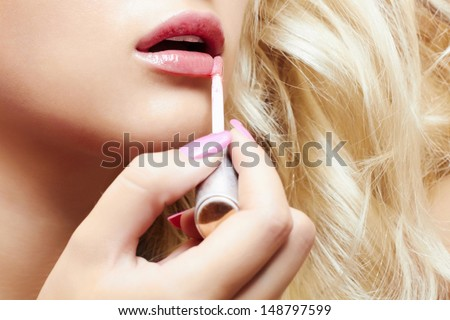 beautiful blond woman paints lips with lipstick. beauty girl. professional make-up. close-up