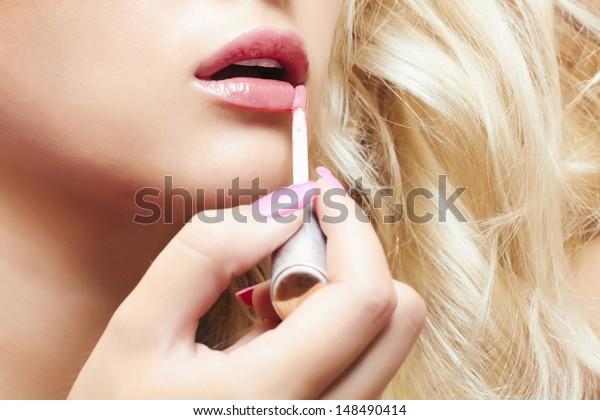 beautiful blond woman paints lips with lipstick