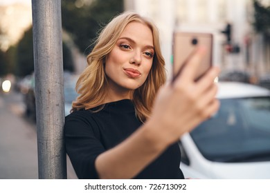 beautiful blond woman is photographing herself at a post in the street on a smartphone