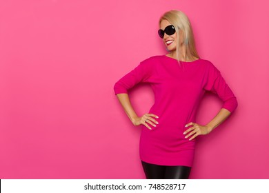 Beautiful blond woman in pink sweater and sunglasses is standing, holding hands on hip and looking away. Three quarter length studio shot on pink background.