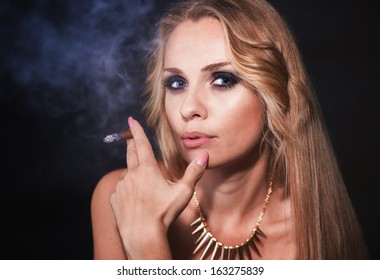 Beautiful blond woman portrait with cigar