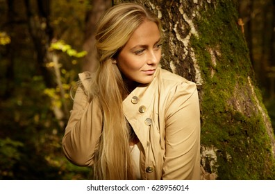 Beautiful blond woman portrait in the forest with birch tree, looking out of frame to the right