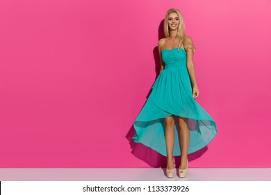 Beautiful blond woman is posing in tuquoise dress and high heels, looking at camera and smiling. Full length studio shot on pink background.