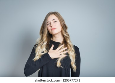 beautiful blond woman promises something, isolated over a gray background
