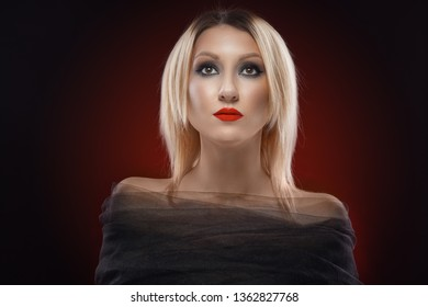 Beautiful blond woman with pure skin. evening make-up on the red background