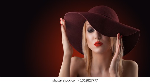 Beautiful blond woman with pure skin. evening make-up on the red background in a red Hat.