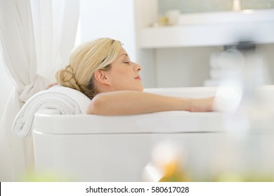 Beautiful blond woman relaxing in bathtub