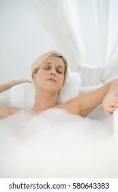 Beautiful blond woman relaxing in bathtub