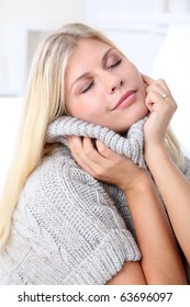 Beautiful blond woman relaxing at home in winter