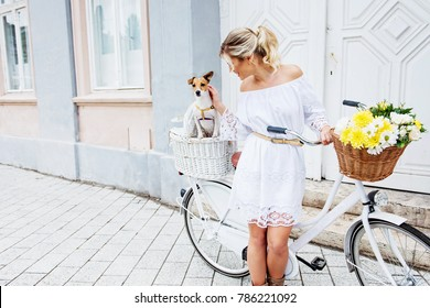 Beautiful, blond woman riding a bicycle in a town with her dog