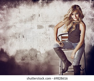 beautiful blond woman in ripped jeans and hair blowing in the wind sitting against grunge wall with space for text.