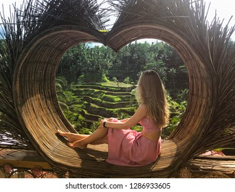 Beautiful blond woman in rose dress sitting on Bali swing. Rice terrace. Ubud. Bali. Indonesia 2019
