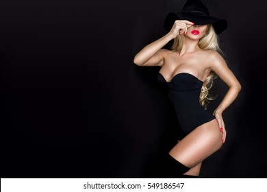 Beautiful blond woman , sexy model with red lips,  dressed in black lingerie outfit body swimsuit and black hat and long boots knee