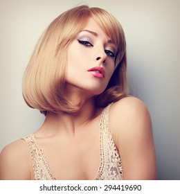 Beautiful blond woman with short hairstyle posing and looking sexy. Color closeup portrait