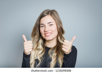 beautiful blond woman showing thumbs up sign, isolated over gray background