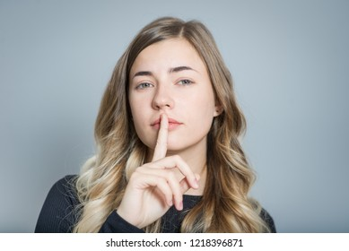 beautiful blond woman shows sign of quiet, secret, isolated over gray background