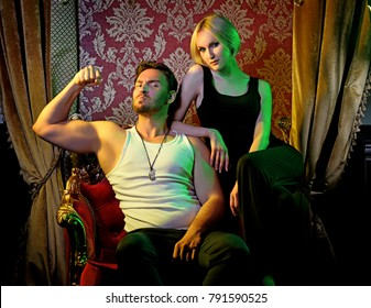 Beautiful blond woman sitting near strong brutal man on a luxury chair in the expensive restaurant