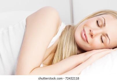 beautiful blond woman sleeping on the white linen