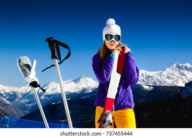 beautiful blond woman smiling in bright colored ski suit wearing mountain glasses stands against the blue sky and snow-capped mountains with skis and with ski poles