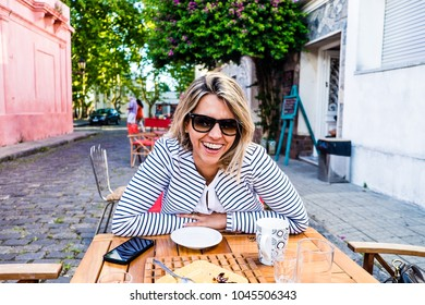 Beautiful blond woman smiling while sitting in bar, drinking cof