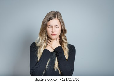 beautiful blond woman with sore throat, isolated over black background