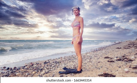 beautiful blond woman standing on the beach in bikini and with swimming goggles