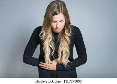 beautiful blond woman with stomach ache, isolated over black background