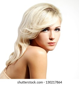 Beautiful blond woman with style hairstyle poses at studio