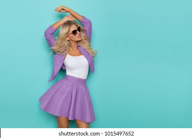 Beautiful blond woman in sunglasses, violet mini skirt and jacket is posing with arms raised and looking away. Three quarter length studio shot on turquoise background.