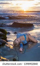 beautiful blond woman at sunset on the coast