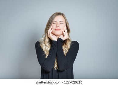 beautiful blond woman touches her clean face with eyes closed, happy, isolated over gray background