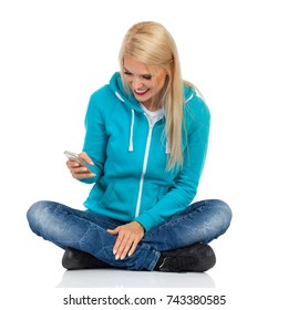 Beautiful blond woman in turquoise sweater and jeans is sitting legs crossed on floor, holding cell phone, looking at it and smiling. Front view. Full length studio shot isolated on white.